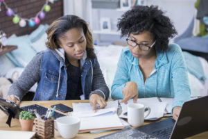Two young women looking at financial information.