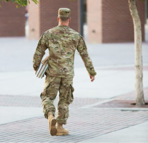US soldier in uniform walking towards a building with books under his arm