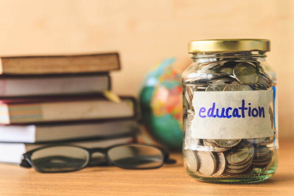 A jar labeled Education with cash inside on a table next to books, glasses, and a globe.